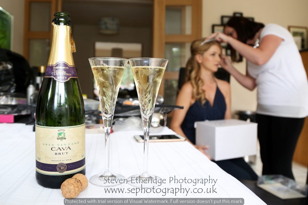 Surrey Wedding Photographer - bride having her hair done with champagne
