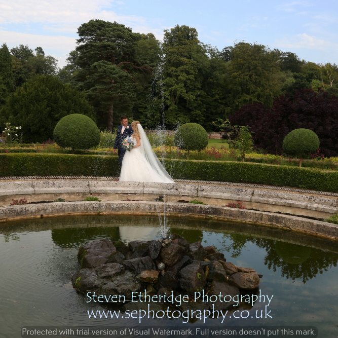 Surrey Wedding Photographer - bride and groom walking past fountain