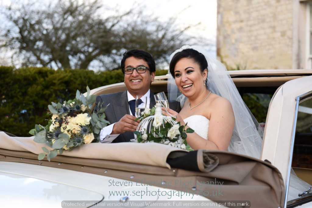 Hampshire Wedding Photographer - bride and groom in open top wedding car