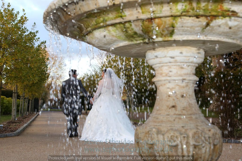 Hampshire Wedding Photographer - bride and groom with fountain