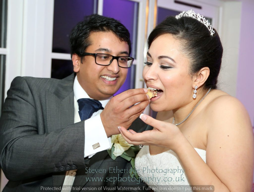 Hampshire Wedding Photographer - bride and groom sharing wedding cake