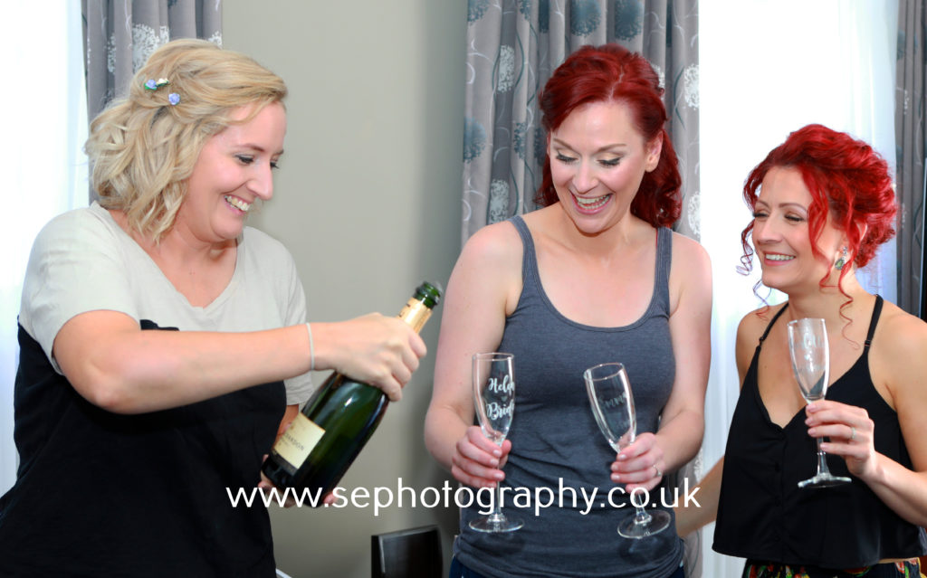 Surrey Wedding Photographer - bride and bridesmaids champagne