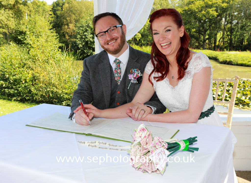 Surrey Wedding Photographer - bride and groom signing register
