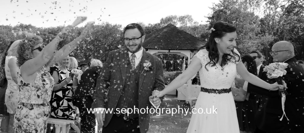 Surrey Wedding Photographer - bride and groom confetti